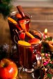 Stäng sig upp av jul funderat vin med frukter, stearinljus och kryddar bakgrund Vintervärmedrink Två kuper royaltyfria foton