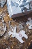 Stäng sig upp av julpynt, den silver slågna in julgåvan och garneringar på en träbakgrund royaltyfri foto