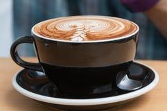 Stäng sig upp av kaffekoppen med cappuccinokaffe och mjölka fradga överst arkivfoto