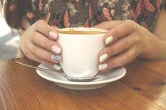 Stäng sig upp av av kaffekoppen och händer royaltyfri fotografi