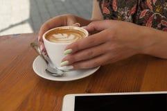 Stäng sig upp av av kaffekoppen och händer royaltyfria bilder