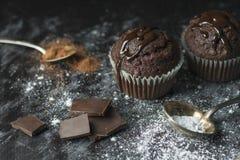 Stäng sig upp av kakaomuffin med chokladisläggning på lantlig tabell c royaltyfria foton