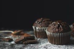 Stäng sig upp av kakaomuffin med chokladisläggning på lantlig tabell c royaltyfri bild