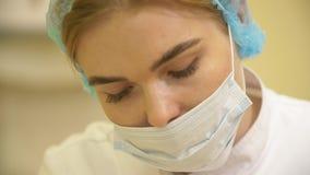 Stäng sig upp av kirurgen som fungerar på en patient st?ende av en kirurg p? arbete I den medicinska maskeringen stock video