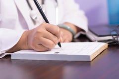 Stäng sig upp av knubbig kvinnlig doktor som handen skriver receptrecept på papperet med pennan royaltyfria bilder