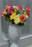 Stäng sig upp av konstgjorda blommor i vas vid den allvarliga stenen Arkivfoto