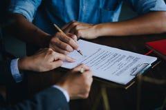 Stäng sig upp av kunden som undertecknar ett pappers- dokument för köpande hus royaltyfria foton