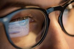 Stäng sig upp av kvinna i exponeringsglas som ser skärmen arkivfoto