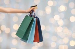 Stäng sig upp av kvinna med den shoppingpåsar och kontokortet Royaltyfri Fotografi