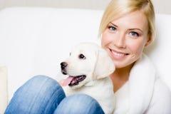 Stäng sig upp av kvinna med den vita labrador valpen fotografering för bildbyråer