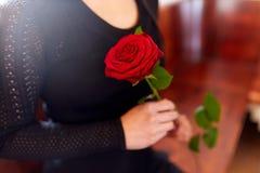 Stäng sig upp av kvinna med rosor på begravningen i kyrka Royaltyfri Bild