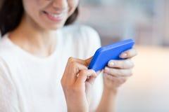 Stäng sig upp av kvinna med smartphonen på kafét Arkivbilder