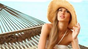 Stäng sig upp av kvinna på hängmattan på den exotiska stranden