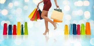 Stäng sig upp av kvinna på höga häl med shoppingpåsar arkivbild