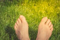 Stäng sig upp av kvinnafot på det gröna gräset arkivfoto