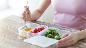Stäng sig upp av kvinnan som äter grönsaker från behållaren stock video