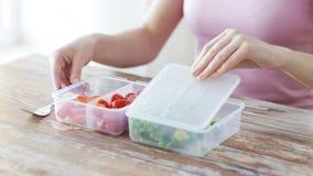 Stäng sig upp av kvinnan som äter grönsaker från behållaren arkivfilmer