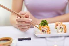 Stäng sig upp av kvinnan som äter sushi på restaurangen Arkivbilder