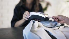 Stäng sig upp av kvinnan som betalar för kläder med kreditkorten stock video