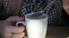 Stäng sig upp av kvinnan som rör en dryck för irländskt kaffe i en råna på moderiktig matställe i kafé stock video