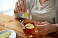 Stäng sig upp av kvinnan som tillfogar ingefäran till te med citronen Royaltyfri Foto