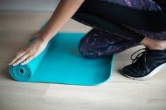 Stäng sig upp av kvinnan som ut rullar övningen Mat On Floor Before Exercise arkivfoto