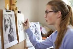 Stäng sig upp av kvinnlig tonårs- bild för den konstnärSitting At Easel teckningen av hunden från fotografiet i kol arkivfoton
