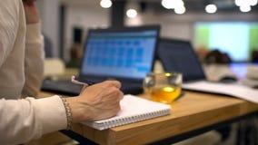 STÄNG SIG UPP av kvinnlign som tar anmärkningar i föreläsningsteater mot bakgrunden av bärbara datorn Närbild av hållande pennor  arkivfilmer