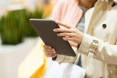 Stäng sig upp av kvinnor med minnestavlaPC och shoppingpåsar Arkivbilder