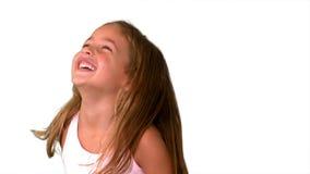 Stäng sig upp av lilla flickan som skrattar och som är roterande på vit bakgrund stock video