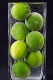 Stäng sig upp av limefrukter i vase med vatten Royaltyfri Bild