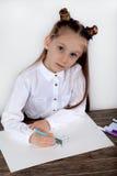 Stäng sig upp av liten flicka i den vita blusen som fokuseras på teckning Förskolebarnet lär hur man drar Dagis och skola Fotografering för Bildbyråer