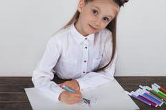 Stäng sig upp av liten flicka i den vita blusen som fokuseras på teckning Förskolebarnet lär hur man drar Dagis och skola Royaltyfri Fotografi