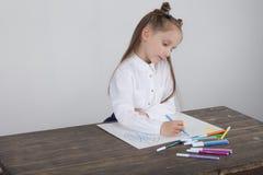 Stäng sig upp av liten flicka i den vita blusen som fokuseras på teckning Förskolebarnet lär hur man drar Dagis och skola Royaltyfria Foton