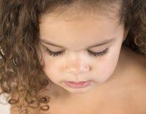 Stäng sig upp av litet barn med lockigt brunt hår arkivfoto