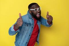 Stäng sig upp av lycklig afrikansk man med den öppnade munnen som poserar i studio arkivfoton