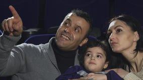 Stäng sig upp av lyckliga älska hållande ögonen på filmer för en familj på bion arkivfoto