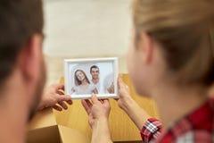 Stäng sig upp av lyckliga par som ser familjfotoet Royaltyfria Foton