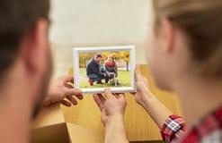 Stäng sig upp av lyckliga par som ser familjfotoet Royaltyfri Bild