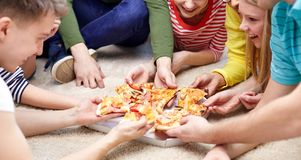 Stäng sig upp av lyckliga vänner som hemma äter pizza Fotografering för Bildbyråer