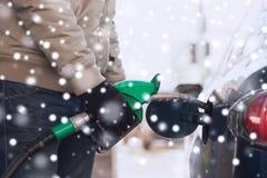 Stäng sig upp av man med dysan för bränsleslangen som tankar bilen Arkivbilder