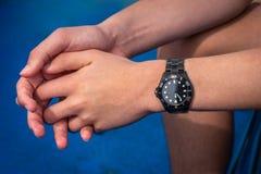 Stäng sig upp av manliga händer och armar som bär ett svart automatiskt stålarmbandsur royaltyfri fotografi