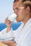 Stäng sig upp av mannen i badrock som dricker kaffe på balkong Arkivfoton