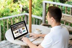 Stäng sig upp av mannen med bärbara datorn som blogging på terrass Royaltyfri Foto
