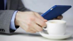 Stäng sig upp av mannen med minnestavlaPC som dricker kaffe arkivfilmer