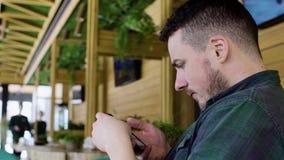 Stäng sig upp av mannen som använder smartphonen i kafé stock video