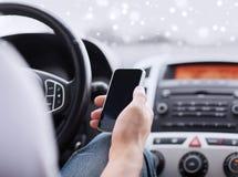 Stäng sig upp av mannen som använder smartphonen, medan köra bilen Arkivfoton