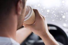 Stäng sig upp av mannen som dricker kaffe, medan köra bilen Arkivbilder