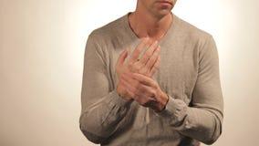 Stäng sig upp av mannen som masserar hans handled på vit bakgrund sjukvård- och problembegrepp stock video