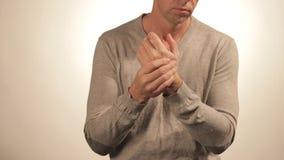 Stäng sig upp av mannen som masserar hans handled på vit bakgrund sjukvård- och problembegrepp arkivfilmer